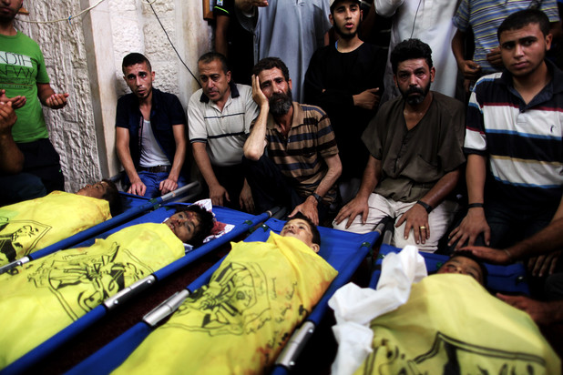 Palestinians mourn over the body of boys from the Baker family, whom medics said was killed with three other children from the same family by a shell fired by an Israeli naval gunboat