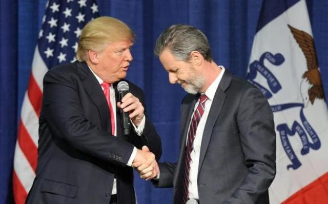 File Photo: U.S. Republican presidential candidate Donald Trump shakes hands with Jerry Falwell Jr. at a campaign rally in Council Bluffs, Iowa